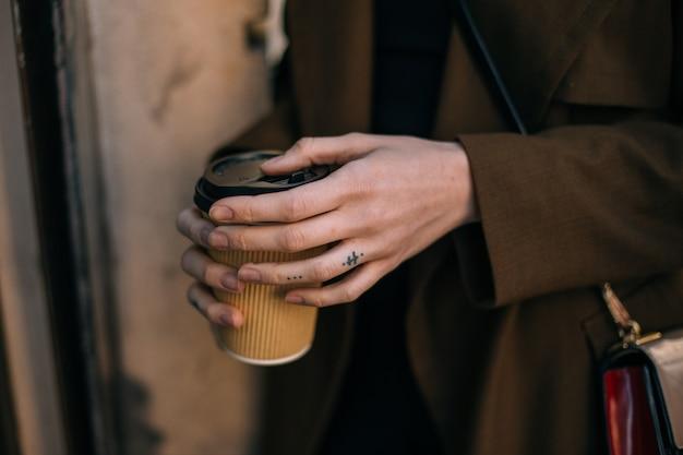 Vrouw houdt afhaalmaaltijden om koffiekopje op straat te gaan