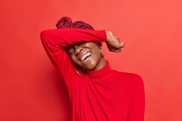 Vrouw houdt arm op hoofd kantelt hoofd glimlacht positief gekleed in casual poloneck voelt zich erg blij lacht om iets grappigs geïsoleerd op rood