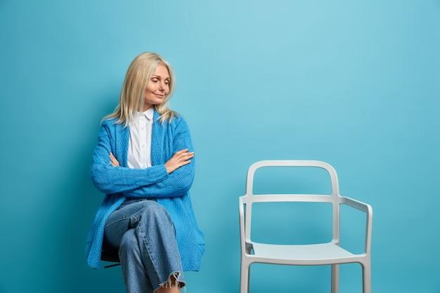 Vrouw houdt armen gekruist kijkt naar lege stoel draagt casual trui en spijkerbroek brengt tijd alleen door geïsoleerd op blauw