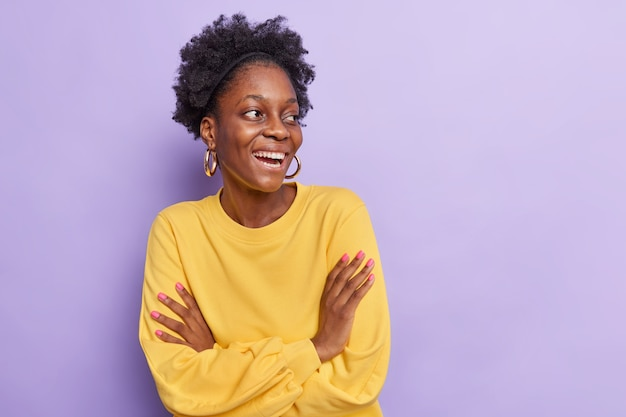 Vrouw houdt armen gevouwen heeft vrolijke conversatie met iemand kijkt weg carefee draagt gele trui geïsoleerd op paarse studio muur lege lege ruimte voor tekst