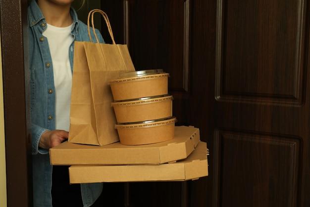 Vrouw houdt bezorgcontainers voor afhaalmaaltijden