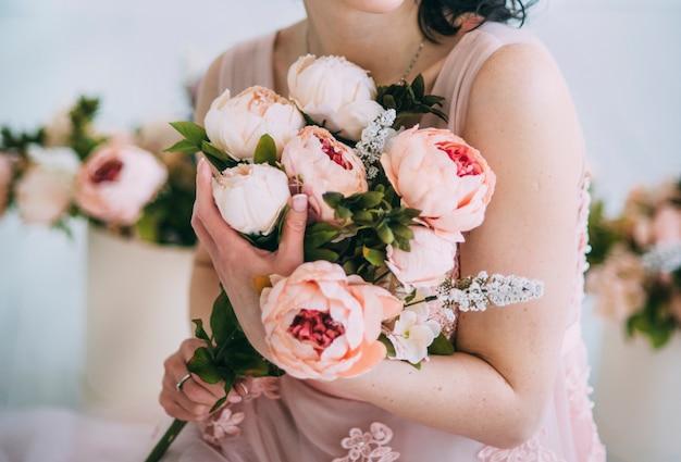 Vrouw houdt bloemen in mooie jurk