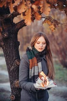 Vrouw houdt boek met vlam in de handen