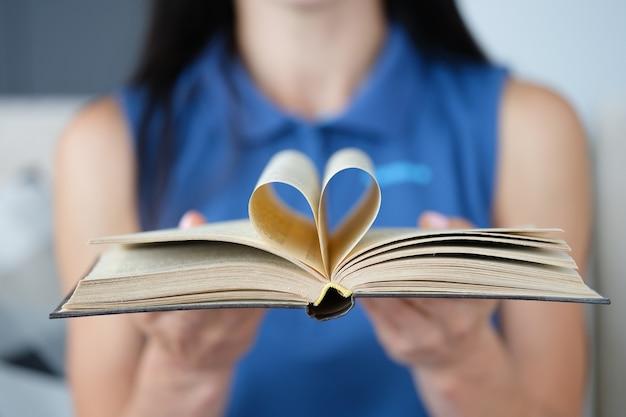 Vrouw houdt boek vast met een pagina in de vorm van een hart gevouwen in het midden