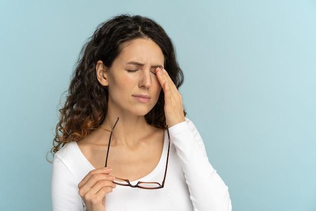 Vrouw houdt bril ogen wrijven, voelt zich moe na het werken op laptop, lijdt aan oogziekten