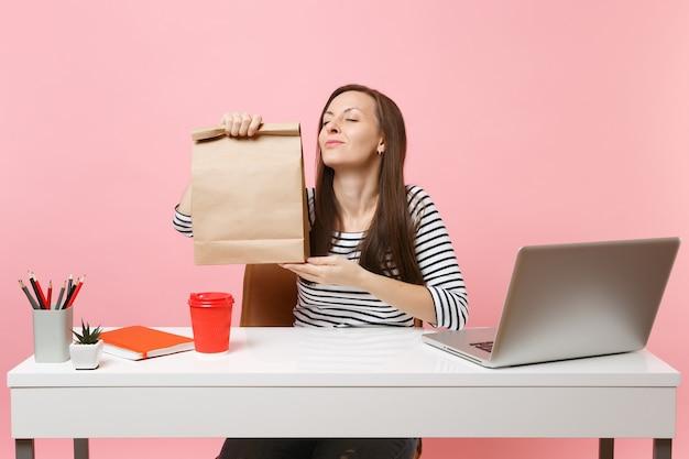 Vrouw houdt bruine, doorzichtige lege lege ambachtelijke papieren zak, ruikende geur op kantoor met pc-laptop geïsoleerd op roze achtergrond. koeriersdienst voor het bezorgen van voedselproducten van winkel of restaurant naar kantoor.