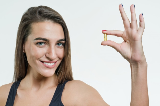 Vrouw houdt capsule met vitamine e, visolie