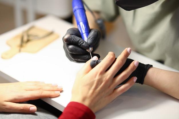 Vrouw houdt de hand van de cliënt vast en verwerkt de nagelriem met een speciaal apparaat