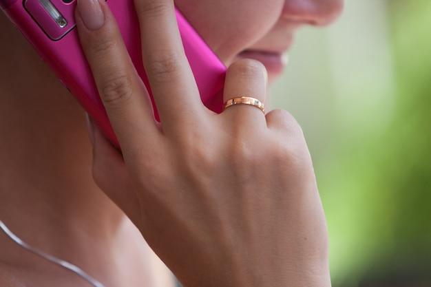 Vrouw houdt de mobiele telefoon vast.