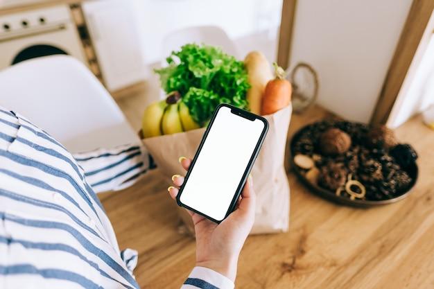 Vrouw houdt de smartphone met wit scherm vast, mock up. online voedselmarktconcept.