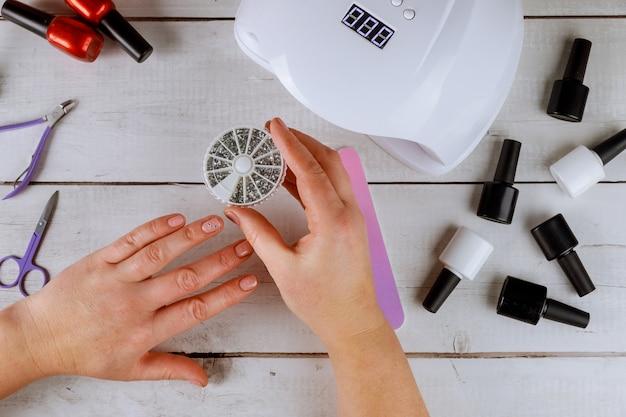 Vrouw houdt doos met manicure strass