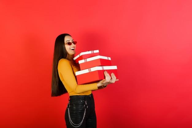 Vrouw houdt drie rode geschenkdozen geïsoleerd op rode studio achtergrond.
