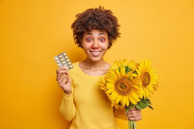 Vrouw houdt drugs vast en boeket zonnebloemen lijdt aan allergische rhinitis en roodheid van ogen die terloops gekleed zijn geïsoleerd op levendig geel