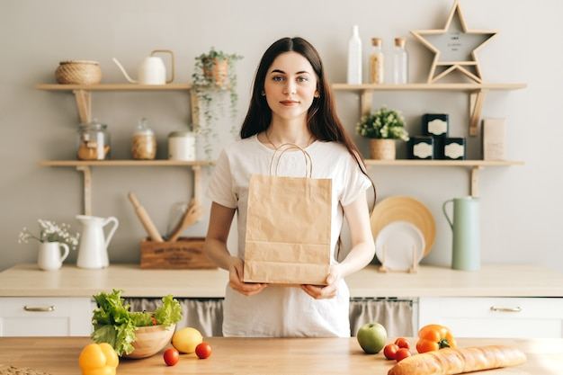 Vrouw houdt eco boodschappentas met verse groenten in de keuken