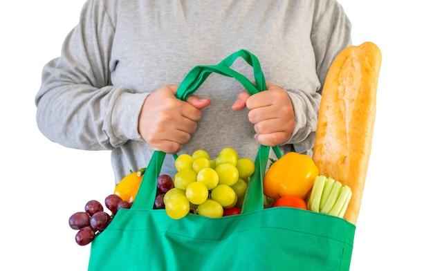 Vrouw houdt eco-vriendelijke groene herbruikbare boodschappentas gevuld met volledig vers fruit en groenten kruidenierswinkelproduct