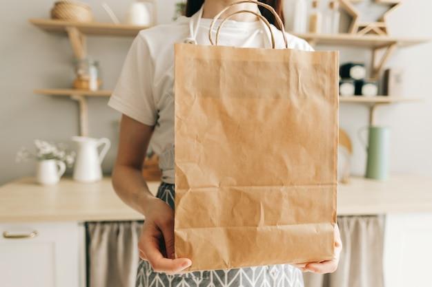 Vrouw houdt eco winkelen papieren zak met voedsel en groenten in handen in de keuken levering voedsel af te halen