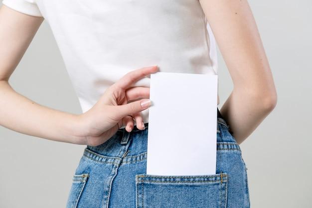 Vrouw houdt een blanco flyer in haar broekzak