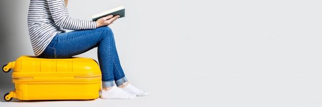 Vrouw houdt een boek en zit op een gele plastic koffer op een lichte ruimte. reizen concept.
