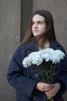 Vrouw houdt een boeket blauwe anjers