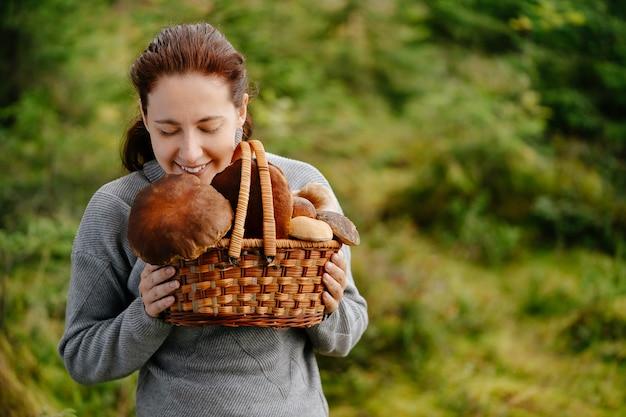 Vrouw houdt een bosoogst in een rieten mand met paddenstoelen gevonden concept biologisch voedsel