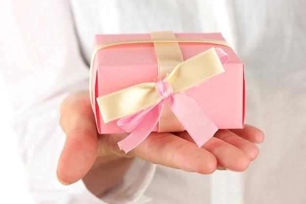 Vrouw houdt een doos met een geschenk op een witte achtergrond close-up