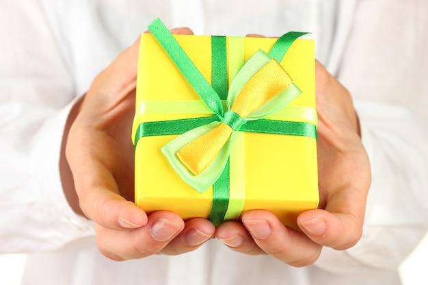 Vrouw houdt een doos vast met een close-up van een cadeau als achtergrond