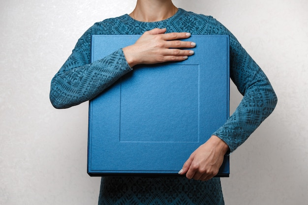 Vrouw houdt een familie fotoboek in stijlvolle designer vierkante doos. vrouwelijke handen die vierkante fotodoos voor huwelijksalbum houden. grote blauwe geschenkdoos in handen van de vrouw close-up met kopie ruimte voor tekst