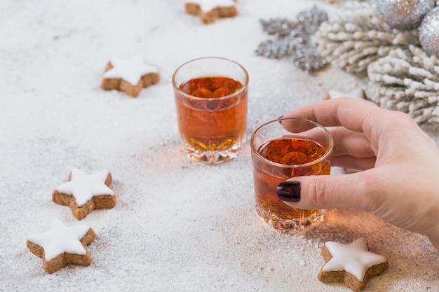Vrouw houdt een glas whisky, cognac of sterke drank vast. koekjes, drankjes en winterdecoraties voor de feestdagen op witte achtergrond. seizoensgebonden vakantie concept.