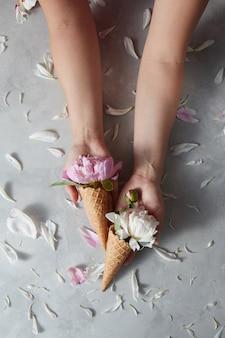 Vrouw houdt een glazen bekers met mooie roze, witte bloemen pion in een wafel kegels in haar handen en bloemblaadjes op een grijze stenen tafel, kopie ruimte.