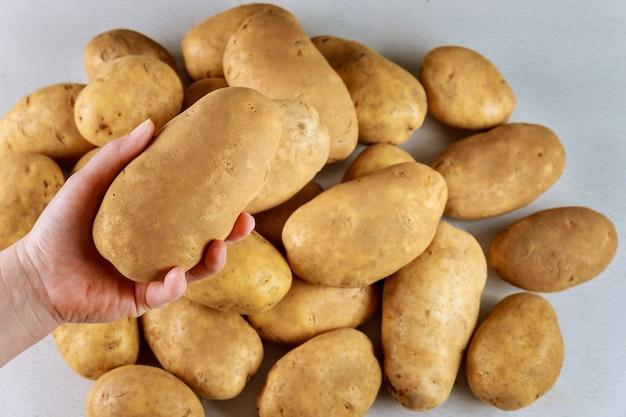 Vrouw houdt een grote aardappel in de hand