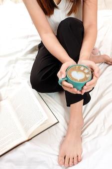 Vrouw houdt een hete late kunst of thee in de ochtend.