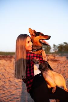 Vrouw houdt een hond in haar armen.