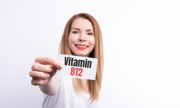 Vrouw houdt een kaart met woord vitamine b12 op wit.