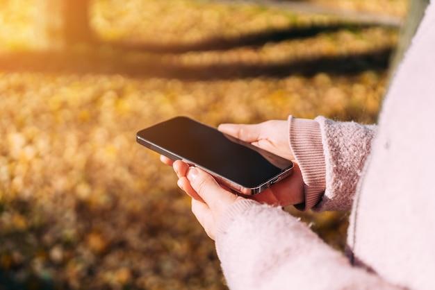 Vrouw houdt een moderne smartphone in haar handen.