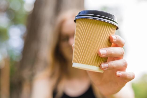 Vrouw houdt een papieren koffiekopje. afhaal- of leveringsconcept. ruimte kopiëren. zomer levensstijl. plaats voor uw tekst of logo op mok, mockup