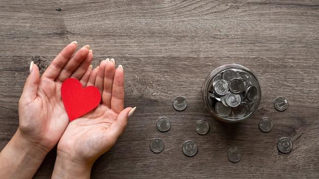 Vrouw houdt een rode haard het blikje met metalen munten