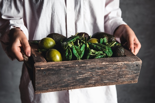 Vrouw houdt een smoothie met spinazie, avocado en limoen in een vintage doos
