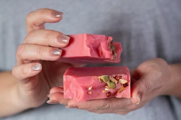 Vrouw houdt een stapel zelfgemaakte handgemaakte zeep. cherry cider. kleine bedrijven, biologische producten, natuurlijke ingrediënten.