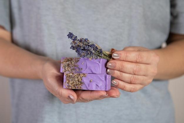 Vrouw houdt een stapel zelfgemaakte handgemaakte zeep. lavendelgeur. kleine bedrijven, biologische producten, natuurlijke ingrediënten.