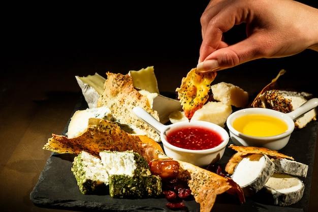 Vrouw houdt een stuk kaas over de kom met cranberrysaus