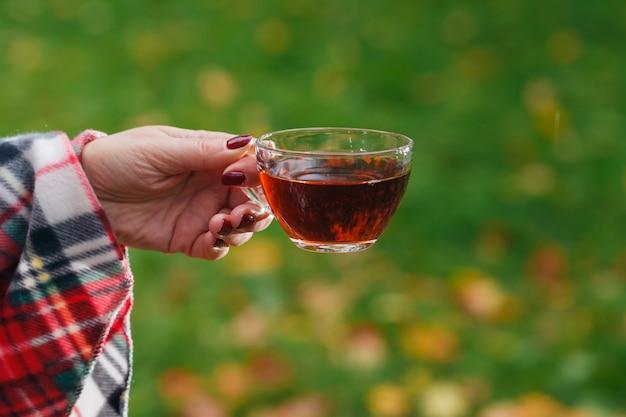Vrouw houdt een thee in de herfst park
