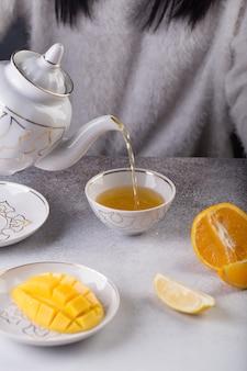 Vrouw houdt een theepot met thee in haar hand en giet die in een kopje