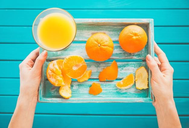 Vrouw houdt een vintage dienblad met mandarijnen en vers sap in haar handen