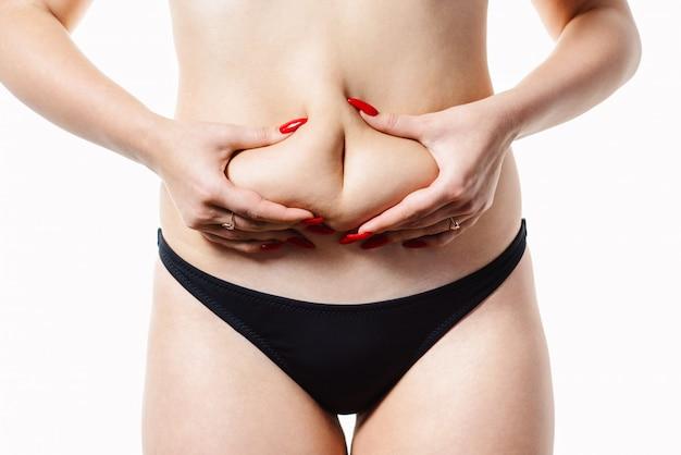 Vrouw houdt een vouw van vet op haar taille. conceptueel beeld van obesitas. close-up, dat op een wit wordt geïsoleerd
