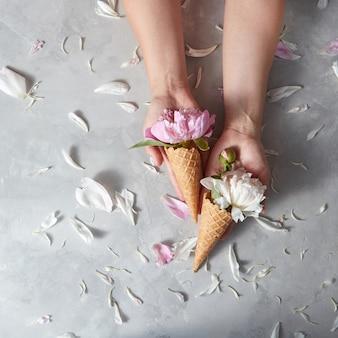 Vrouw houdt een wafelbekers met prachtige roze, witte bloemenpion in haar handen. bloemblaadjes op een grijze stenen achtergrond, plaats voor tekst.