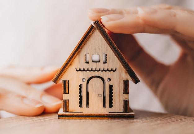 Vrouw houdt en beschermt een houten huis met haar handen met de zon op een lichtroze achtergrond. lief huis