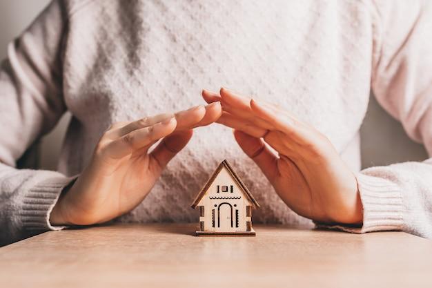 Vrouw houdt en beschermt een houten huis met haar handen met de zon op een lichtroze ruimte