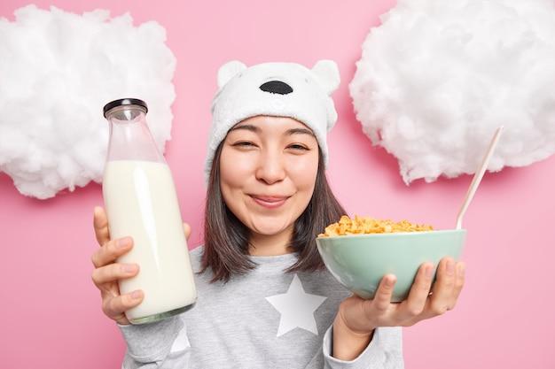 Vrouw houdt fles melk en cornflakes, gekleed in een casual pyjama, gaat ontbijten na het ontwaken geniet van het begin van de nieuwe dag