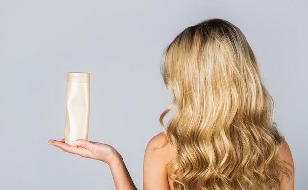 Vrouw houdt fles shampoo en conditioner. vrouw met shampoo fles.