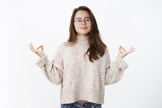 Vrouw houdt geduld, is kalm en vredig terwijl ze poseert in een trui en een bril die naar voren kijkt, glimlachend in lotushouding staat met mudra-gebaar, mediteert of yoga doet voor ontspanning van de geest.